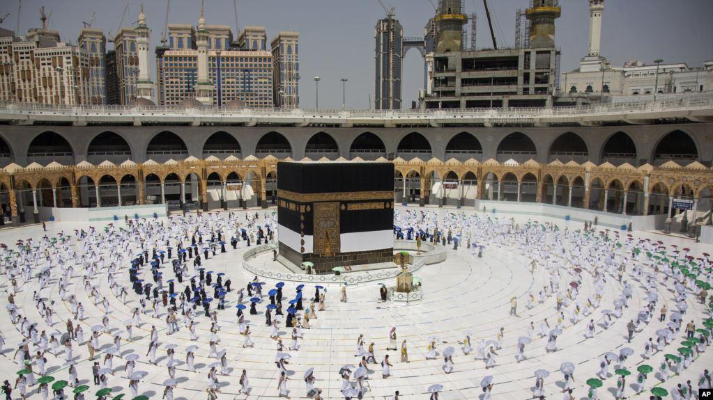 Jemaah haji yang jumlahnya dibatasi karena pandemi Covid-19, bergerak mengelilingi Ka'bah berbentuk kubus dengan menjaga jarak, dalam ritual pertama pelaksanaan haji, di Mekkah, Arab Saudi, 29 Juli 2020. (Saudi Media Ministry via AP)