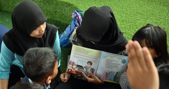"Seorang relawan Indonesia membacakan buku untuk anak-anak ketika mereka mengikuti program di perpustakaan bawah jembatan yang disebut ""TBM Kolong"", 10 Februari 2019. (Foto: AFP/Adek Berry)"