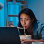 Asia freelance smart business women eating instant noodles while working on laptop in living room at home at night. Happy young Asian girl sitting on desk work overtime, enjoy relax time.